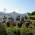 Trapeze marquee on the lawn with outdoor seating area