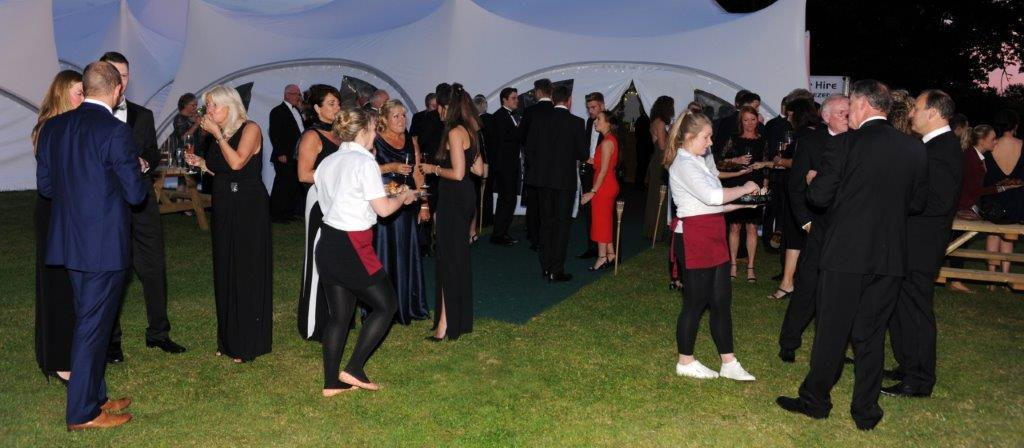 Guests enjoying drinks and nibbles outside a marquee