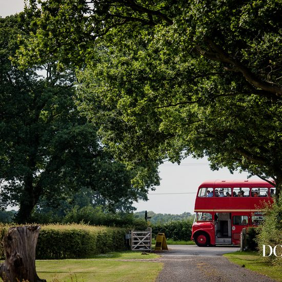 Guests arrive at a rural wedding venue on a double decker bus