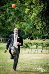 Smart wedding guest kicking a football at a rural wedding